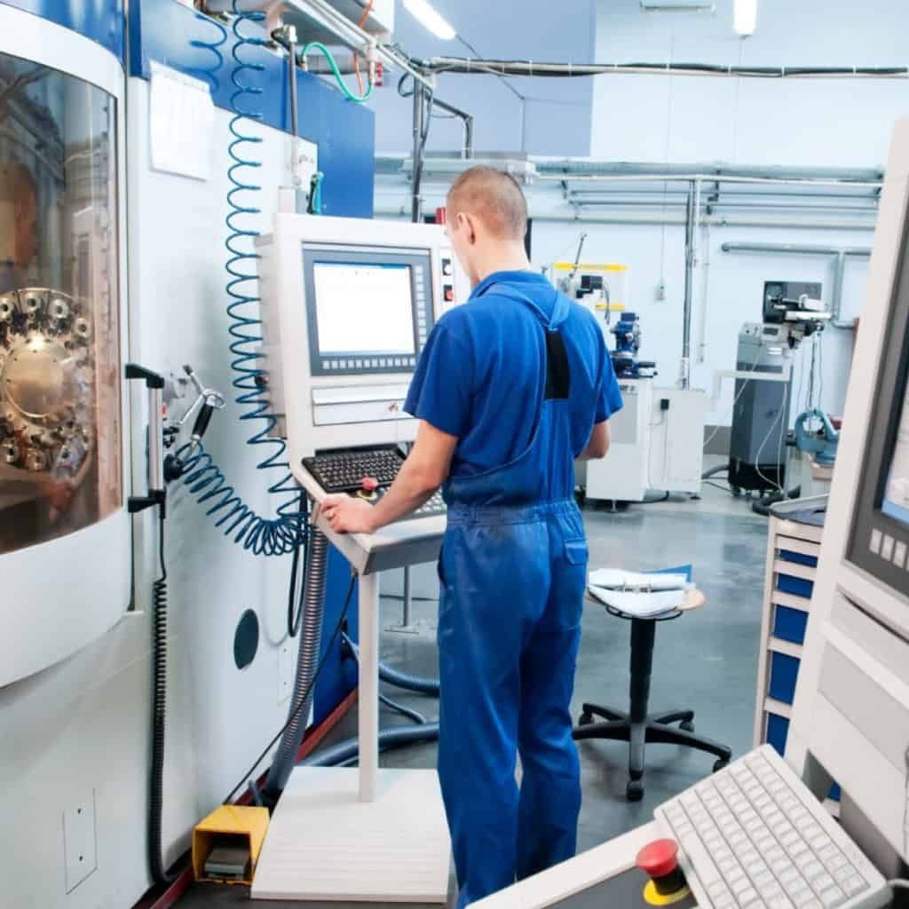 mechanical technician operating cnc milling cutting machine at tool workshop