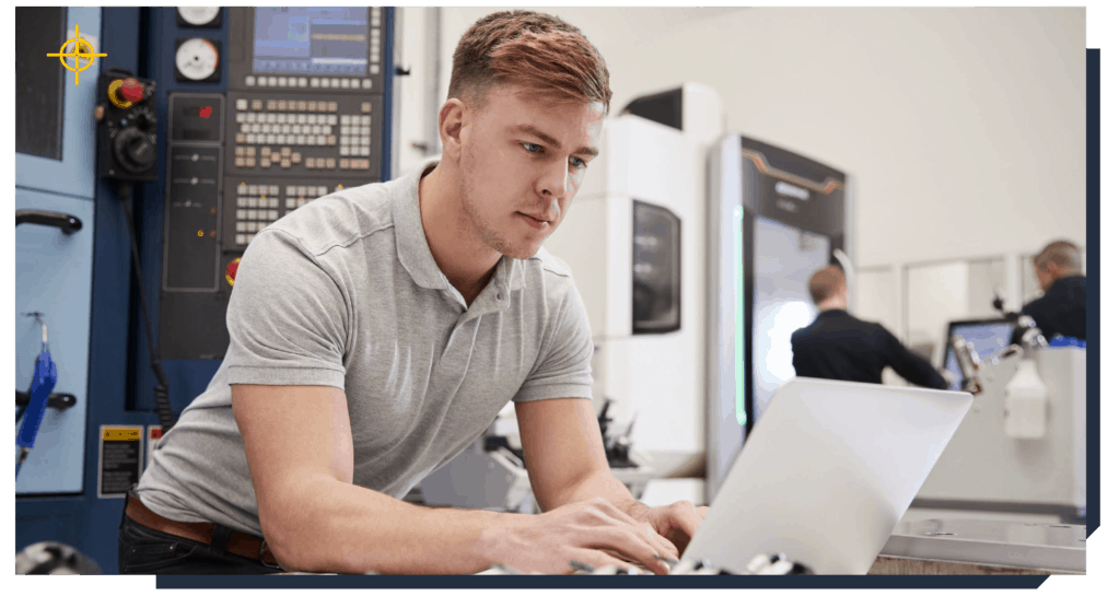 Male technician working on a laptop on factory floor