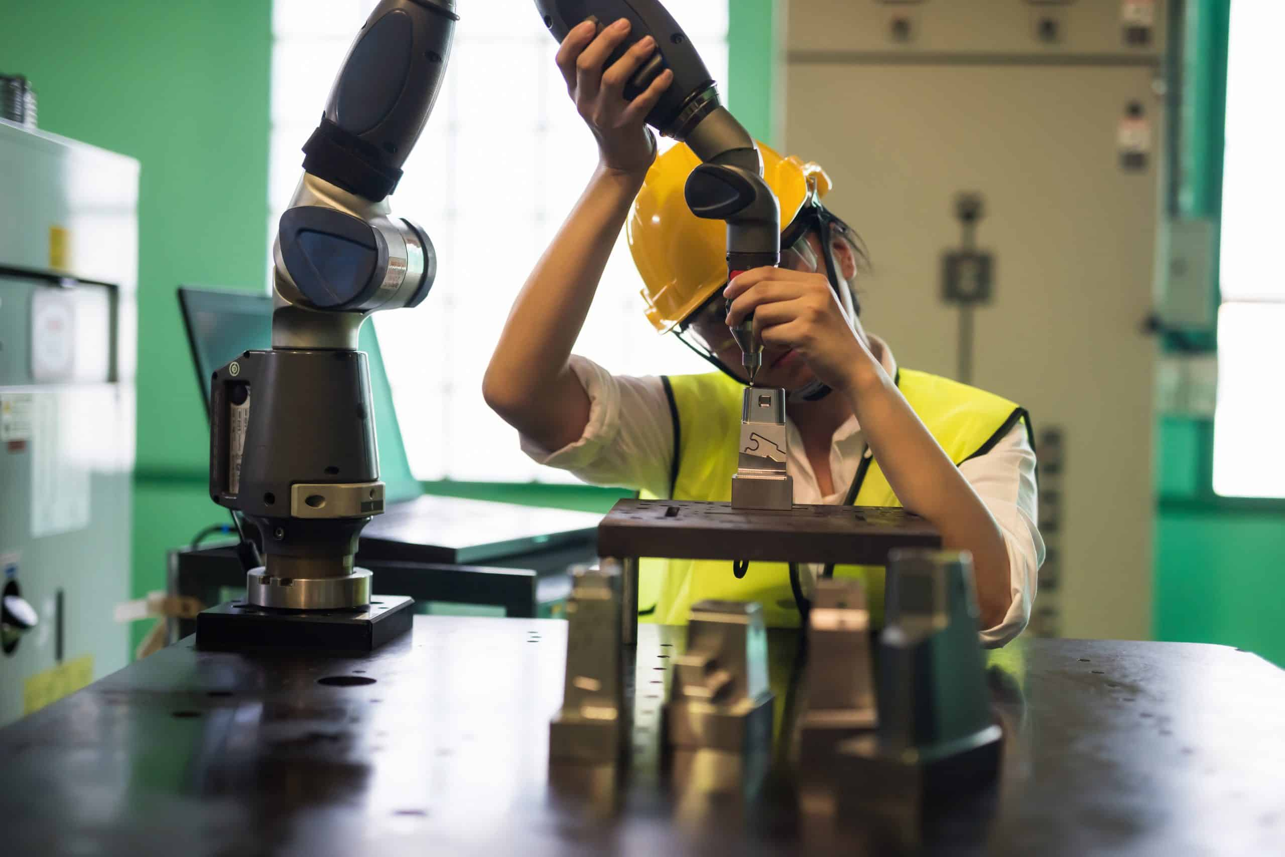 Waist up technician engineer inspector wearing hardhat and protection glasses check Automation lache robot arm in automotive manufacturing factory. Quality control (QC) of safety business process.
