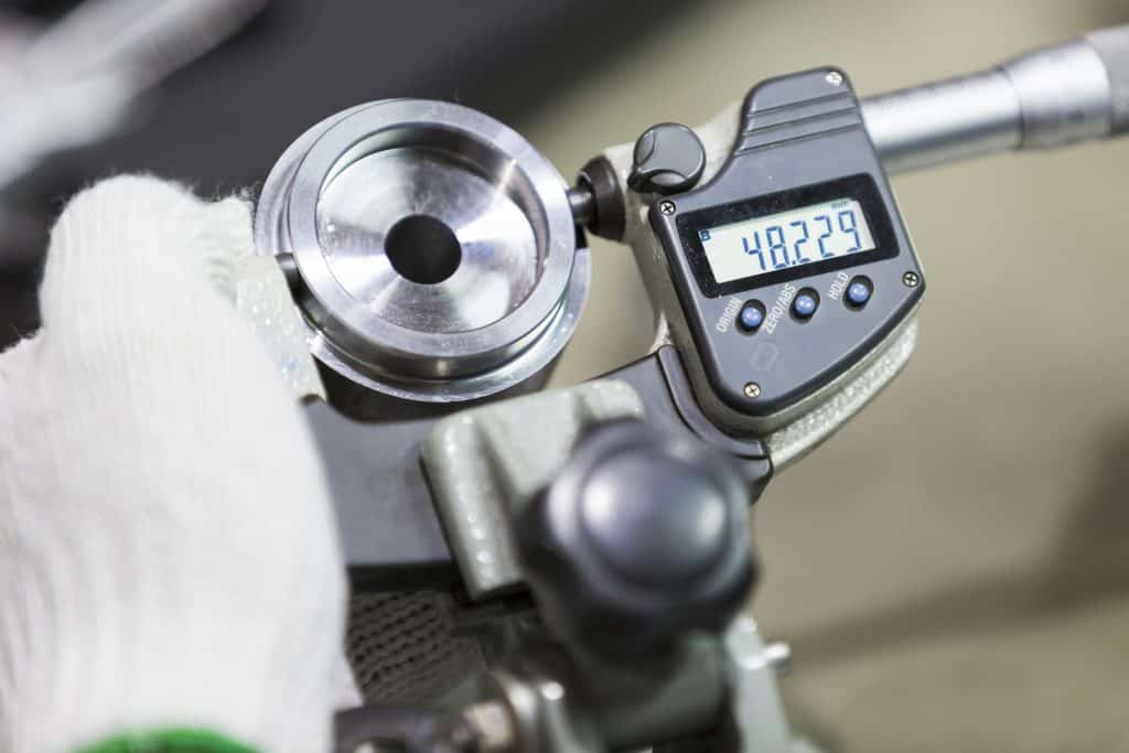 operator inspects high precision automotive part by micrometer