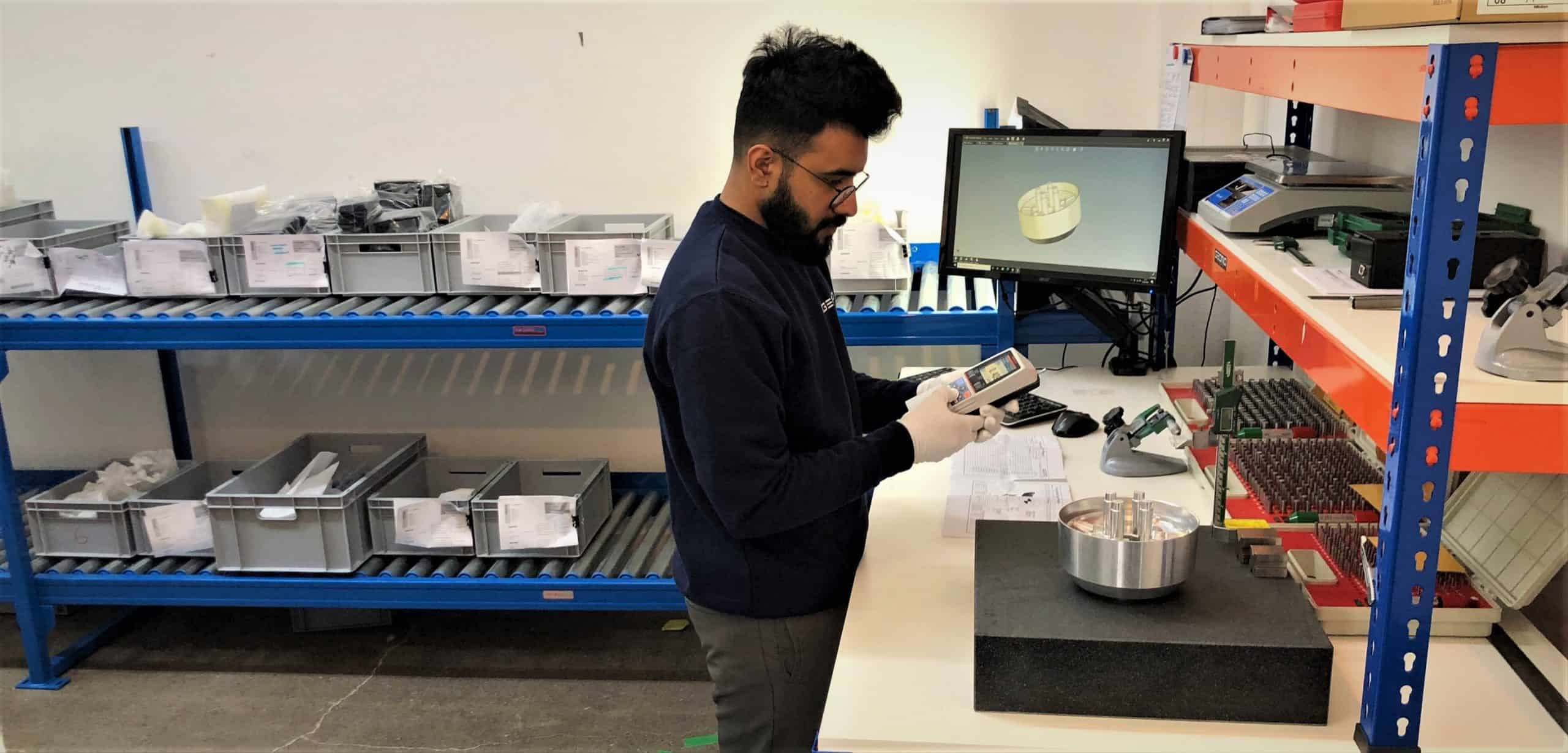 a man in a quality lab inspecting manufacturing parts